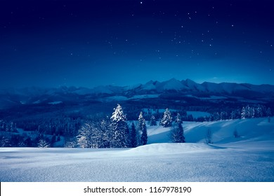 Snowy winter night. Stunning night landscape. Sky with stars over snowy mountains and valley.