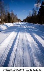 snowy winter road covered in deep snow with car tire tracks going in random directions