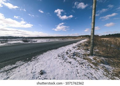 snowy winter road covered in deep snow with car tire tracks going in random directions - vintage retro look