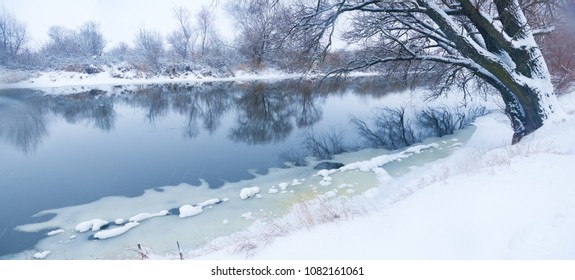 Snowy winter shore of the river in the misty morning.