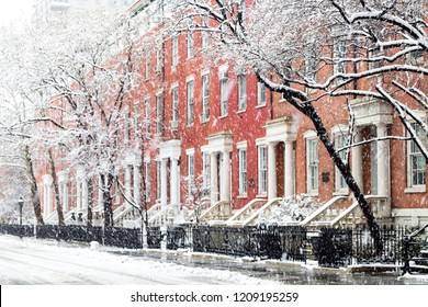 Snowy winter street scene with historic buildings along Washington Square Park in Manhattan, New York City NYC