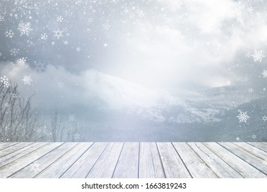 The snowy wooden desk on winter background with snowflakes