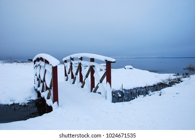 Snowy wooden footbridge across a small creek by the coast of the Baltic Sea on the swedish island Oland