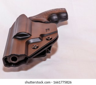 A snub nosed 38 special revolver in a black plastic holster on a white background