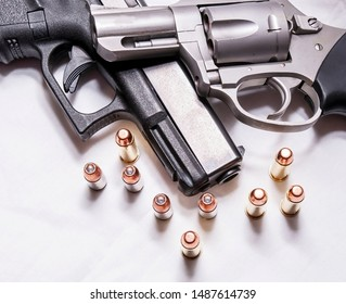 A snub nosed, stainless 357 magnum revolver on top of a black 9mm pistol with several bullets for each caliber in front of them on a white background