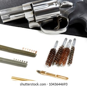 Snubnose revolver laying on table with gun cleaning tools isolated on a black mat