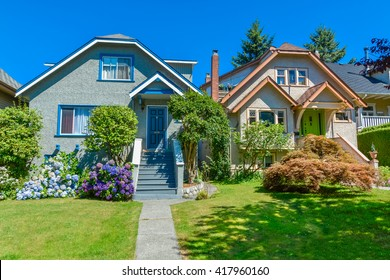 Snug warm family houses side by side. Residential house with the pathway over front yard lawn on blue sky background.