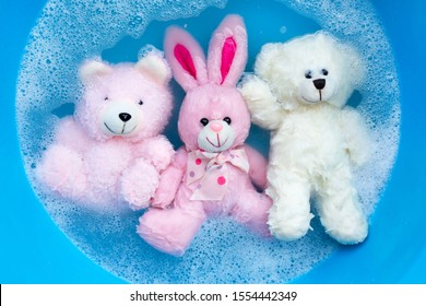 Soak rabbit doll with  toy bears in laundry detergent water dissolution before washing.  Laundry concept, Top view