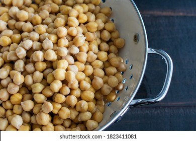 Soaked Chickpeas Drained in a Colander: Dried garbanzo beans that have been soaked in water and drained in a colander