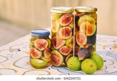 Soaked figs in alcohol liqueur in jars on the table with colorful table-cloth, Portugal