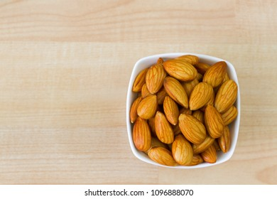 Soaked Shelled Almond in white bowl on wooden background, top view with copyspace