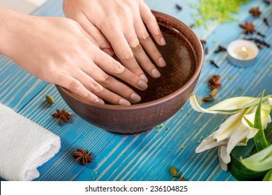 Soaking finger nails in the bath with water on wooden table with spa stuff on background