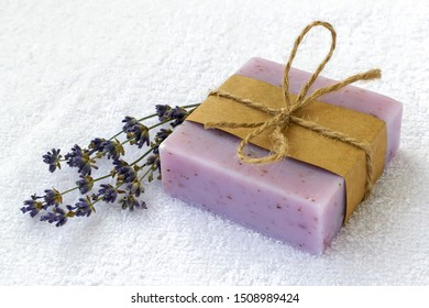 Soap bar with dry aromatic lavender flowers. Purple handmade soap on a white terry cotton towel. Natural toiletries and hygiene products with herbs and essential oils. Front view.