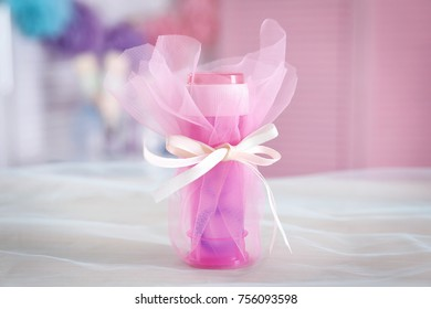 Soap bubble bottle on table against blurred background