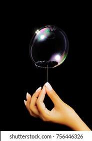 Soap bubble bursting by needle