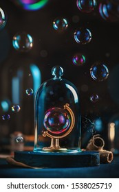 Soap bubble in a globe frame under a glass dome. Ecology and climate change concept. Fragile Earth still life with copy space