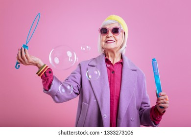 Soap bubbles. Fashionable positive retired woman wearing pink sunglasses enjoying soap bubbles