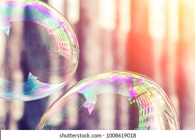 Soap bubbles with reflection of city buildings in the sunlight