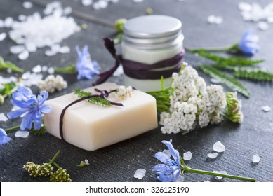 soap, cream and bath salt with chicory and yarrow herbs on black wood table
