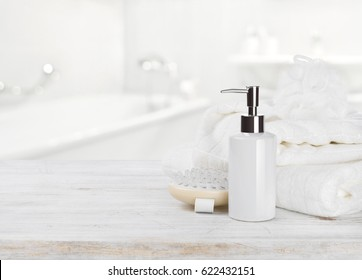 Soap dispencer, towels, massager and wisp of bast over blur
