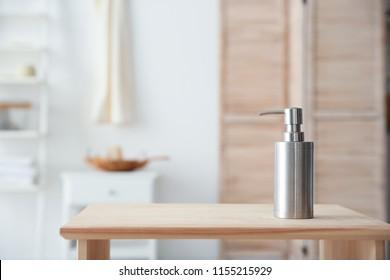 Soap dispenser on table against blurred background