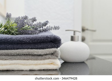 Soap dispenser with a stack of towels in a bathroom closeup