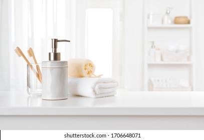 Seifenspender, Zahnbürsten und weißes Handtuch auf der Badezimmertheke