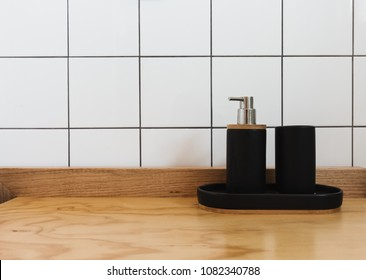 Soap dispenser and tub in black on a wooden vanity in a renovate