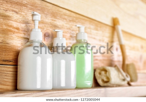 Soap dispensers on wooden shelf. Space for text