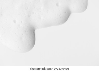Soap foam with bubbles on white background frame with copy space, horizontal. Minimalist hygiene healthcare and medicine background. Shampoo or cleanser texture