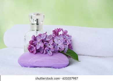 Soap and perfume bottle with lilac flowers over white soft bath towel