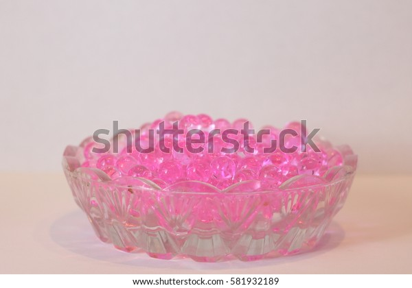 Soap pink fragrant beads in a small saucer