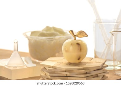 Soap in shape of apple from soy wax on background of ingredients for handmade soaps. Natural cosmetics. Ecological soap. Front view