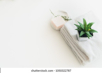 Soap and white cotton towels on white counter table inside a bright bathroom background.  For product display montage.