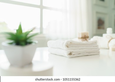 Soap and white cotton towels on white counter table inside a bright bathroom background.  For product display montage