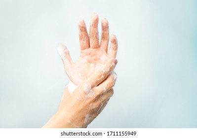 Soapy hands on a blue background