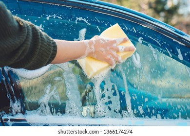 Soapy hands with yellow sponge washing car window outdoors in spring. Spring cleaning, car-wash, summertime, care concept.