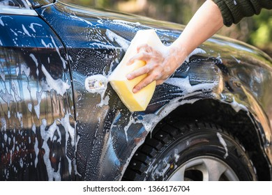 Soapy hands with yellow sponge are washing black car outdoors in springtime. Car, vehicle maintenance, washing, wash concept.