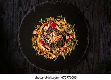 soba noodles of buckwheat Noodles of buckwheat yellow and red pepper, herbs. Pan-Asian cuisine. On stone tray on dark wooden table.