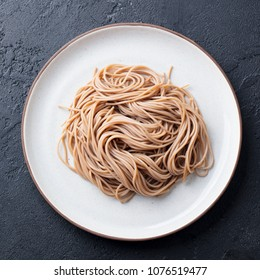 Soba noodles on a white plate. Japanese food. Black slate background. Top view.