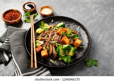 Soba noodles with vegetables and fried tofu in a bowl.