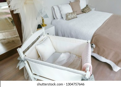 Sober and elegant bedroom with cot with canopy and double bed. Selective focus on cot in foreground