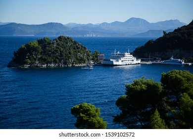 Sobra, Mljet, Croatia - October 6, 2019: A ferry docked at the Sobra port on Mljet island, Croatian coastline in the background.