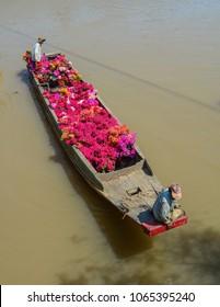 Soc Trang, Vietnam - Jan 31, 2016. A wooden boat carrying flowers on river in Soc Trang, Vietnam.
