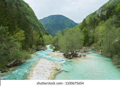 Soca river, also known as the Emerald river flowing down the valley in late spring time. Green hills covered with forests are surrounding the valley.