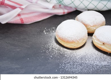 The so-called Krapfen, which are traditionally baked in Germany during the carnival season, lie on a dark surface - donuts sprinkled with powdered sugar