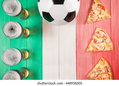 soccer ball, beer and pizza on table in form of Italian flag. creative concept. copy space.