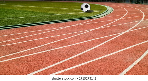 Soccer ball black and white classic with lines on green artificial grass at public outdoor football  stadium with runing track field, sport,