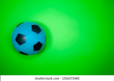 Soccer ball. Blue and black football on plain green background with copy space. Sport and recreation.