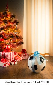 Soccer ball with blue ribbon and christmas tree with gifts on background.